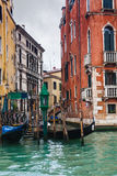 Mooring of gondolas near houses in Venice in rain Royalty Free Stock Photos
