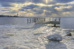 Mooring in ice against a lighthouse in winter royalty free stock image