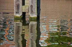 Mooring and its reflection. Wooden pile mooring in Delfshaven, Rotterdam, reflecting in the rippled water of the Schie river Royalty Free Stock Photography