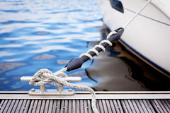 Mooring at a pier. A white yacht moored with a line tied around a metal fixing on the quayside Royalty Free Stock Photos