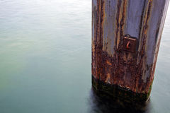 Mooring pole from rusty metal in the sea, long exposure with cop Royalty Free Stock Images