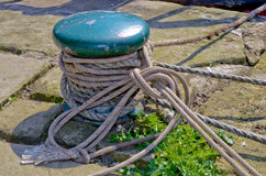Mooring post. By canal almost totally wrapped in rope stock image