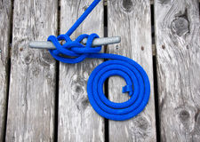 Mooring Rope. Blue mooring line tied to dock Stock Images