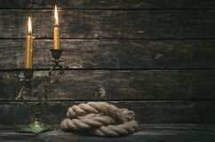 Mooring rope and burning canlde. Mooring rope and burning canlde on aged wooden table of pirate background with copy space stock image