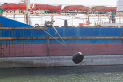 The mooring rope with a cargo vessel loaded Stock Images