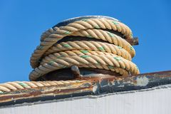 Mooring rope coiled around a bollard at a steel ship. Detail of mooring rope coiled around a bollard at a steel ship against a blue sky royalty free stock photography