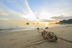 Mooring rope with knots on fine sand in morning which has view of beautiful sea and sky in morning as background. Songkhla Thailand Royalty Free Stock Image