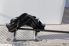 A mooring rope with a knotted end tied around a cleat Stock Images