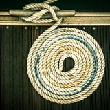 Nautical mooring rope. A mooring rope with a knotted end tied around a cleat on a wooden pier Royalty Free Stock Photography