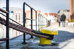 Mooring rope of a large ship standing in the port. Harbor cape wrapped with a mooring rope. Season of the early spring stock image