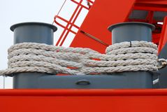 Mooring Rope. A white thick mooring rope coiled around a ship pivots stock images