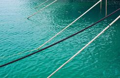 Mooring ropes against Mediterranean gree. N water in the marina of Puerto Portals in Mallorca, Spain Stock Image