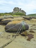 Rocks and mooring ropes on beach Stock Image