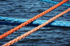 Mooring ropes securing ships. Strong and thick mooring lines (blue and orange) crossing against the blue sea waters Stock Photography