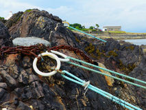 Mooring and tie up rings with ropes for small boats concreted into the rocks on shore at a small private anchorage in Donaghadee c. Mooring and tie up rings with Stock Images