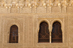 Moorish architecture inside the Alhambra. Arches, grated windows and carved walls inside the Nasrid Palace (Palacio Nazaries), in the complex of the Alhambra Stock Photo