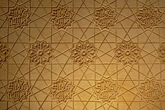 Moorish wall decorations in Nasrid palace, Alhambra, Granada. Moorish wall decoration, pattern with abstract flowers and calligraphy in Nasrid palace, part of stock image