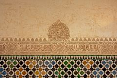 Moorish decorations with stone carvings and tiles on a wall in Nasrid palace, Alhambra, Granada. Moorish wall decorations with stone carvings and colorful tiles Royalty Free Stock Photos