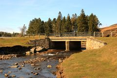 Moorland bridge in sunshine. A road bridge bathed in sunshine on the weardale moorland with shallow water flowing down a rock strewn stream with grassy banks and stock photo