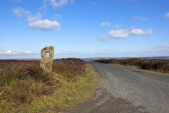 Moorland road with monolith Stock Images