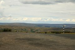 Moorland road posts. Looking across a gravel viewing car park to miles of open moorland with safety posts marking the road under light and dark clouds royalty free stock image