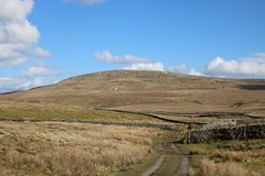 Moorland track, dry stone walls, Fountains fell. View of moorland in the Yorkshire Dales looking along a farm track and footpath towards Fountains Fell with an Royalty Free Stock Photo