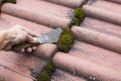 Moos di pulizia del tetto fuori con la spatola fotografia stock libera da diritti