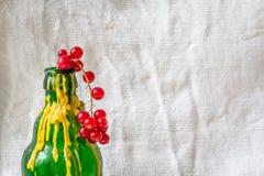 Moosbeeren und eine grüne Flasche mit gelbem Wachs Stockfotografie
