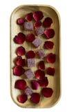 Moosbeermarmelade und rosafarbene Blumenblätter auf einem hölzernen Behälter Lizenzfreies Stockfoto
