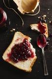 Moosbeermarmelade verbreitet auf Brot Stockfotografie