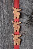 Moose Cookies with the Word JOY. Three moose shaped cookies on a red ribbon with letters spelling out JOY. Vertical and hanging on a rustic wood wall Stock Photos