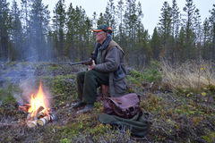 Moose hunter sitting on a stump with a litle fire in front. Royalty Free Stock Images