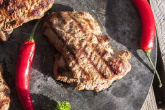 Moose sirloin steak. Between chilis, on a stone table Royalty Free Stock Photo