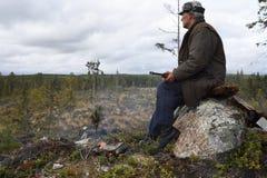 Moosehunter, das auf einem Stein mit einem Feuer vor ihm sitzt Lizenzfreie Stockbilder