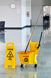 Mop And Bucket With Caution Sign Royalty Free Stock Photography