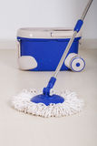 Mop and blue bucket for cleaning floor Royalty Free Stock Photo
