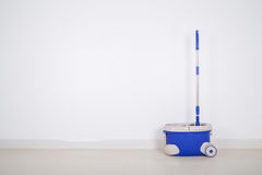 Mop and blue bucket on floor and wall background Stock Photos