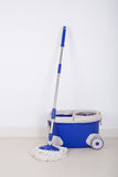 Mop and blue bucket on floor and wall background Stock Images