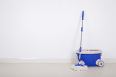 Mop and blue bucket on floor and wall background Stock Photography