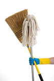 Mop and broom being held by a rubber gloved hand Stock Photo
