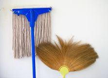 Mop and broom propped against a wall Stock Images