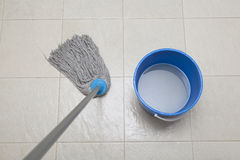 Mop and bucket. Detail shot of a wet floor during cleaning stock image
