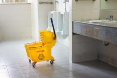 Mop bucket on wet floor in toilet Stock Photos