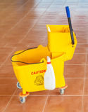 Mop bucket and wringer with caution sign on the floor Royalty Free Stock Photography