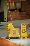 Mop With Caution Sign. Mop and Bucket with caution sign on wet floor Stock Image