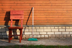 Mop And Chair. Time of rest. Old mop near chair against wooden wall of house Royalty Free Stock Image