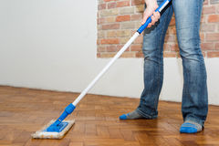 Mop cleaning a wooden floor Royalty Free Stock Image