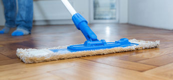 Mop cleaning a wooden floor Stock Images