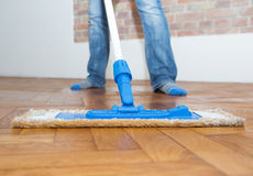 Mop cleaning a wooden floor Stock Photos