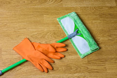 Mop and gloves on wooden floor Stock Photography